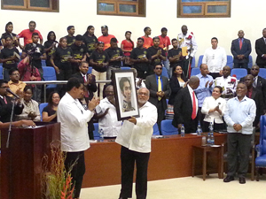 President Donald Ramotar holds aloft a portrait of Simon Bolivar presented to him by Venezuelan President Nicolas Maduro, yesterday, at the International Conference Centre.
