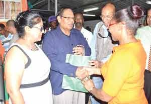Prime Minister Moses Nagamootoo receives a gift from a staff of the Bank of Guyana in the presence of his wife Seeta when they visited the BOG booth.