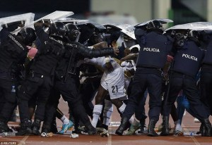 Ghana players are shielded by riot police after being pelted by missiles at half-time Police provide a human shield amid fears over Ghana players' safety in front of the tournament host's fans