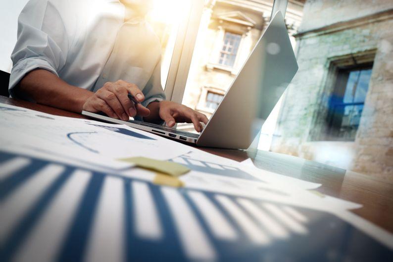 Mann mit Laptop sitzt am Tisch und arbeitet im Internet