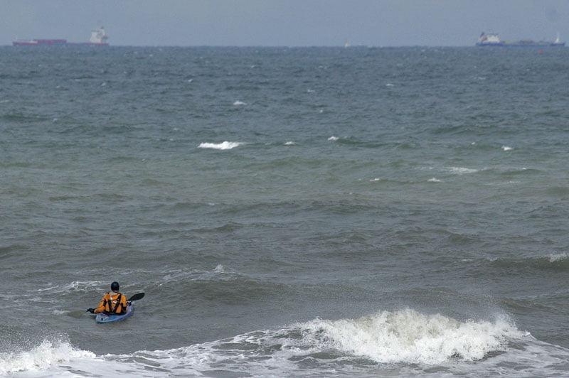 Johan på utsidan av revet, stora båtar i bakgrunden en bit ut
