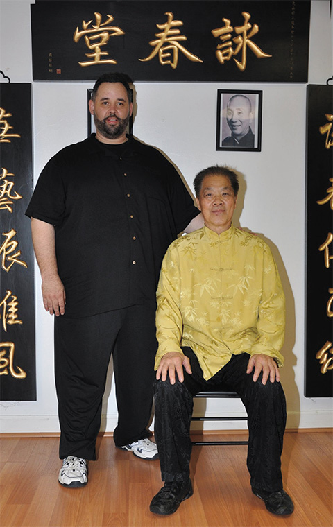 Shannon Moore (left) and grandmaster William Cheung. The picture on the wall shows the face of Ip Man. Picture © Columbia Martial Arts Center LLC and Shannon Moore.