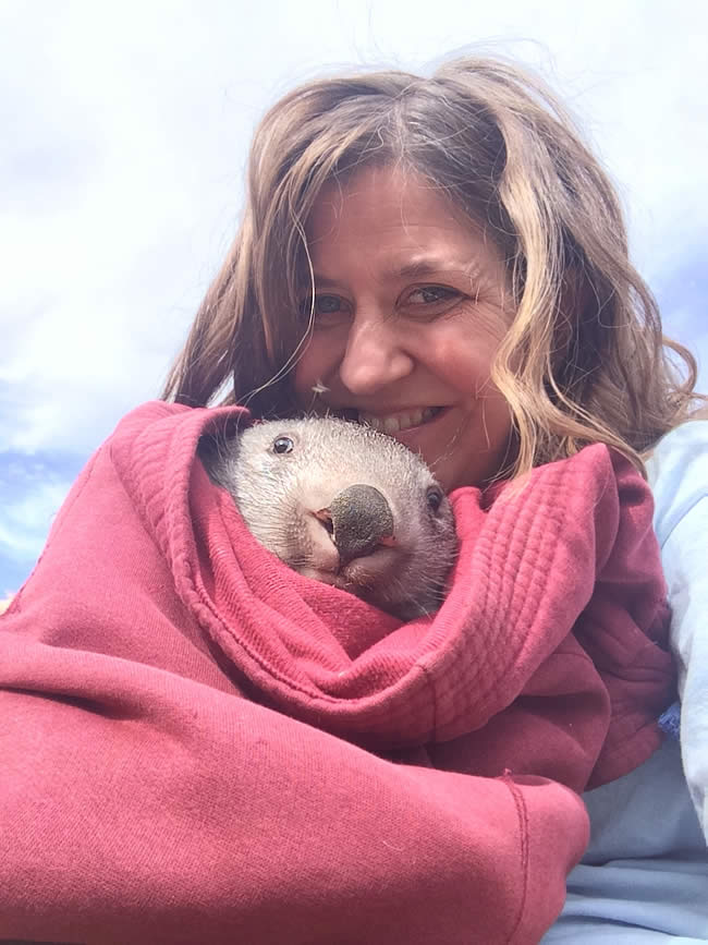 Kama with a bundled-up wombat named Cruiser