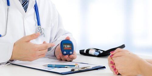Doctor shows glucometer with glucose level
