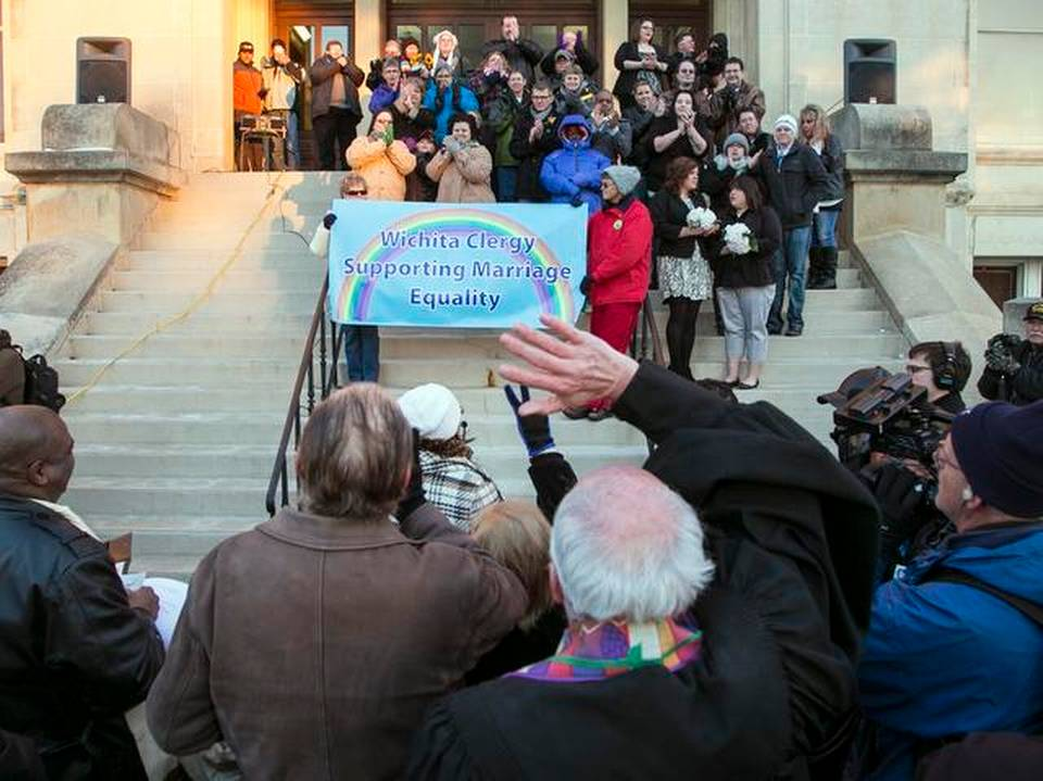 The crowd cheers as about 20 couples marry in a same-sex marriage ceremony on the steps of the Historic Sedgwick County Courthouse in Wichita, Kan., Monday, Nov.17, 2014.