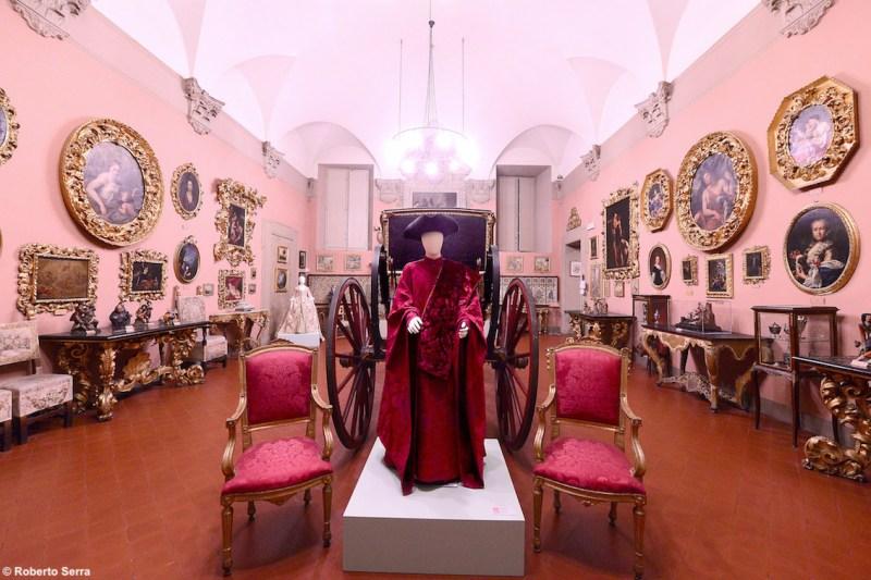 Nella foto, la suggestiva carrozza Berlina di gala, un manichino vestito con abiti settecenteschi e oggetti e suppellettili della stessa epoca.