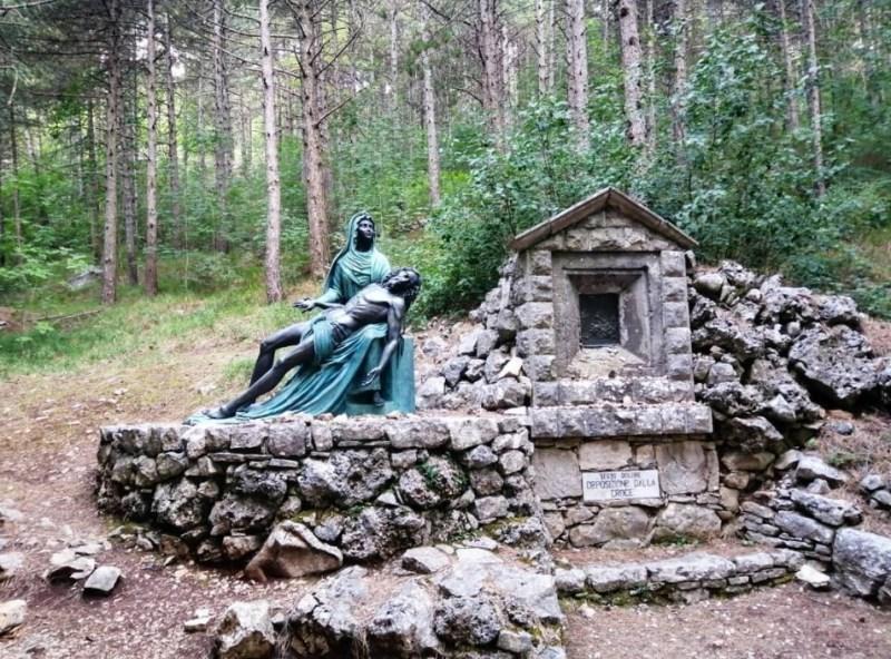 Rappresentazione scultorea della Madonna che regge tra le braccia il corpo esamine di Gesù in una composizione toccante al centro della radura.