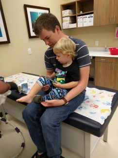 Stefen holding Blake while he has his cast removed
