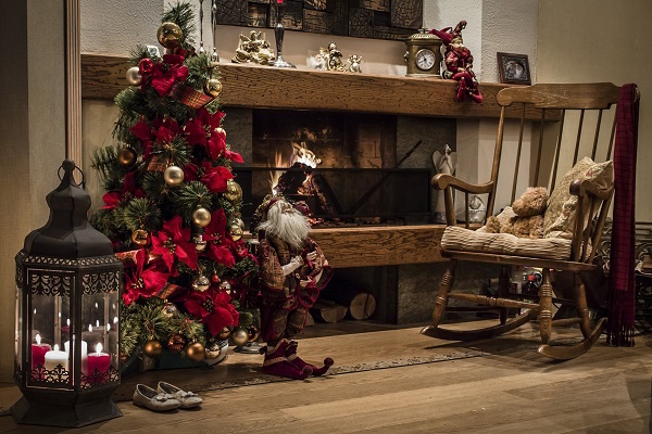 Christmas tree, candelabre and chear with teddy bear near fireplace