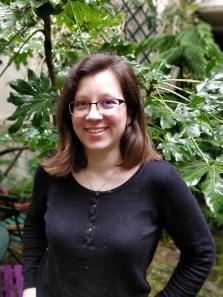 Une photo en buste de l'autrice, devant un fond de plantes
