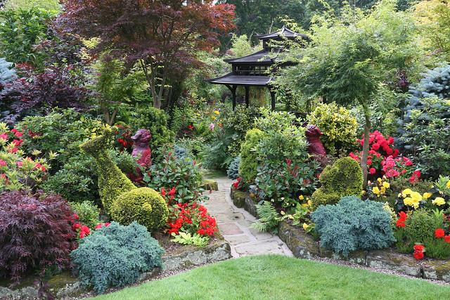 Image décorative : un jardin très chargé en espèces végétales, contenante une pagode japonisante.