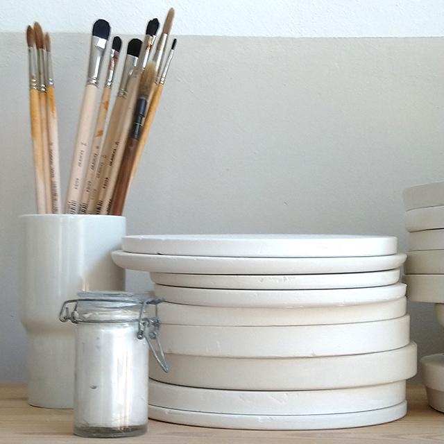 Pinsel fuer Porzellanworkshops in einem Porzellanbecher neben einem Stapel Gipsplatten und einem Glaeschen Schlicker