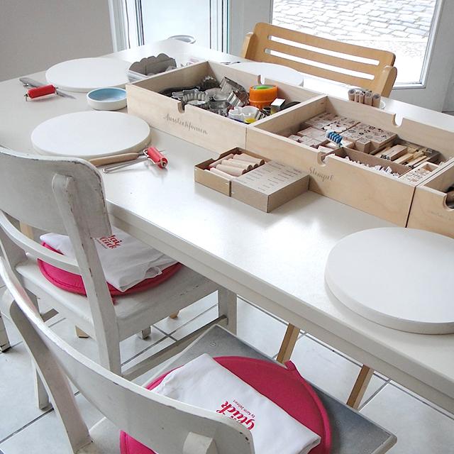 So sieht es aus, bevor ein Workshop startet. Ein Tisch mit vorbereiteten Stempeln, Ausstechformen und Gipsplatten