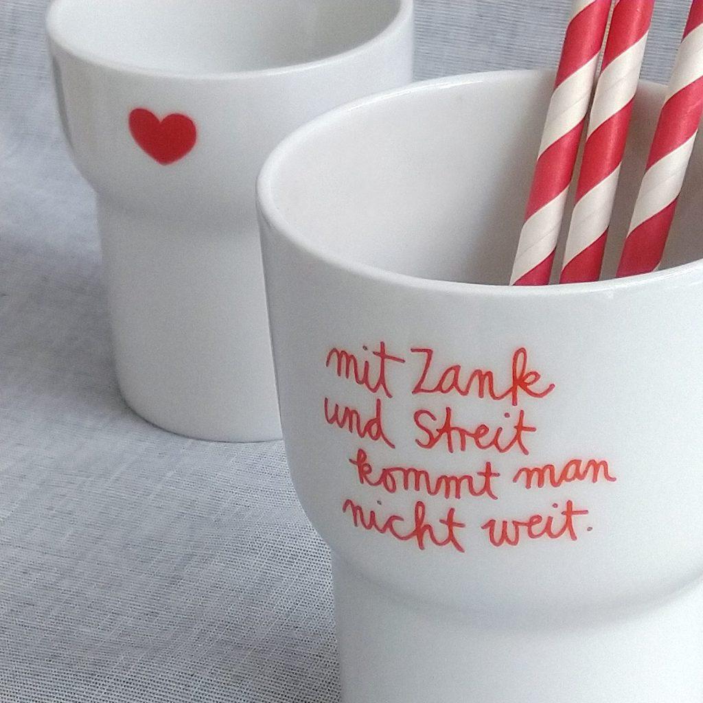 """2 weiße Porzellanbecher mit roten Dekoren: """"Herzchen"""" und """"mit Zank und Streit kommt man nicht weit"""""""