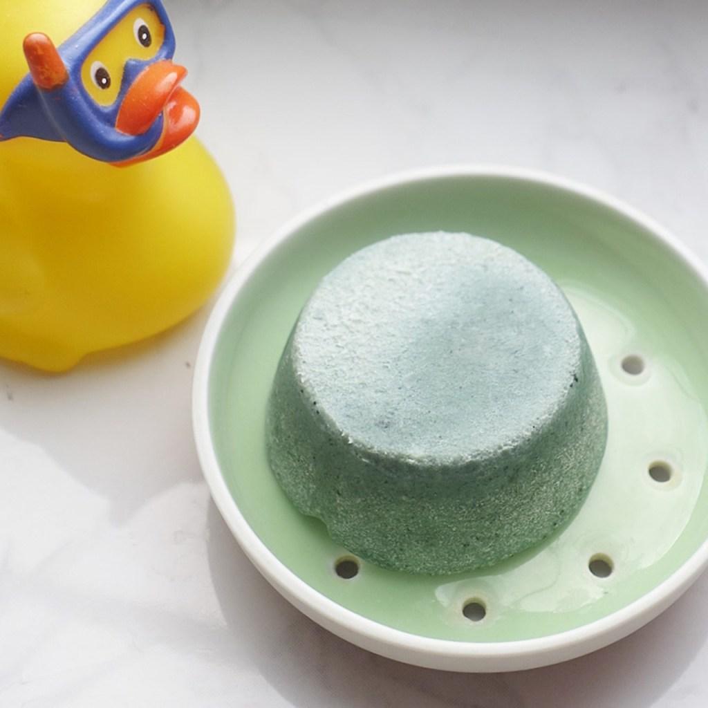 1 grasgruene Seifenschale aus Porzellan mit einem Stück Haarseife von Beti.Lue zu Leipzig, daneben eine Bade-Ente