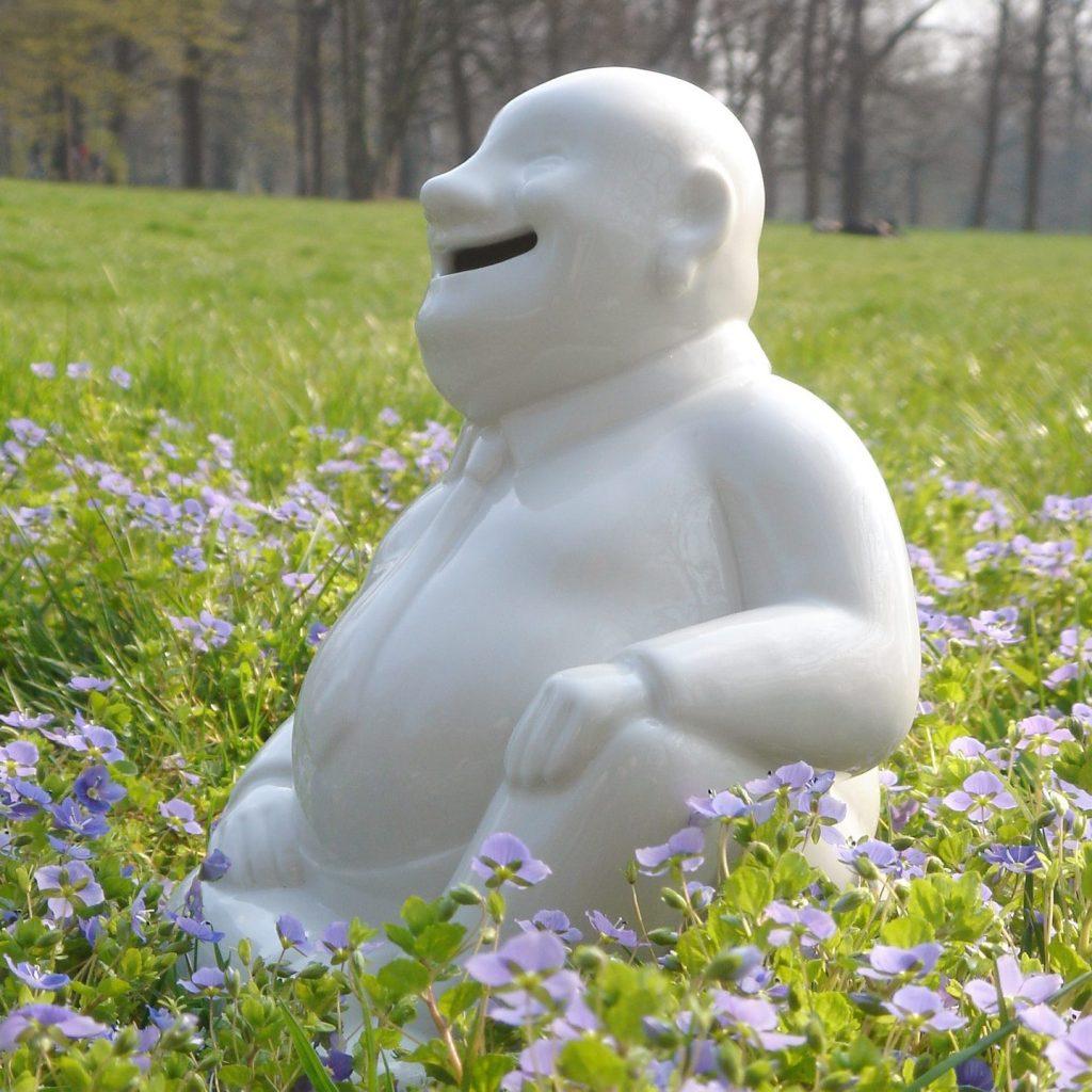 """Spardose aus Porzellan """"Buddhy"""" sitzt auf der Wiese im Sonnenlicht"""