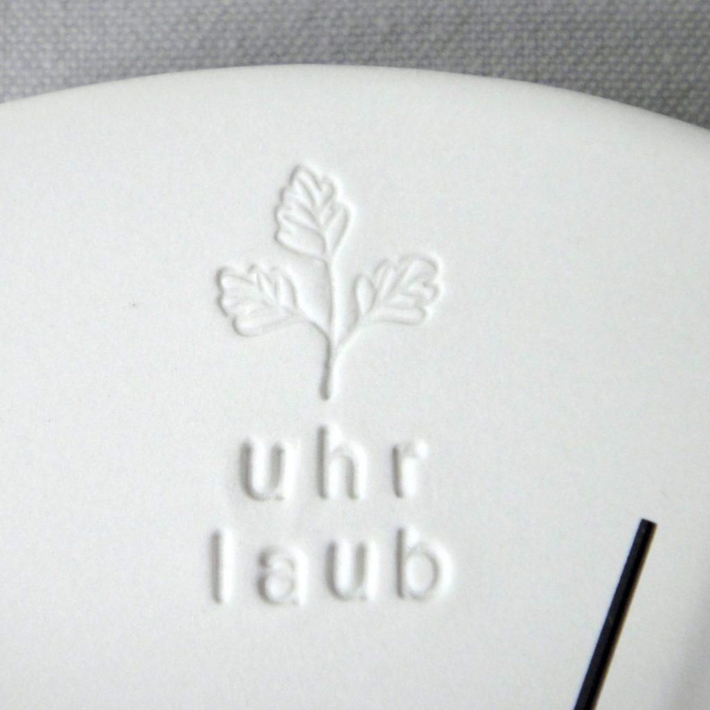 Detail einer Porzellanuhr, gestempeltes Motiv von Laub - Uhr-Laub