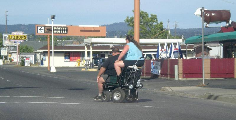 Two Large People Riding One Wheelchair 1360850692