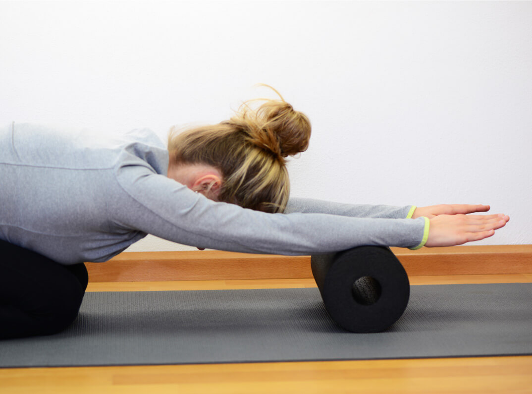 Frau macht Faszienmassage mit Faszienrolle am Unterarm