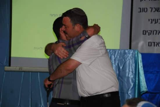 Hugging a student at graduation.