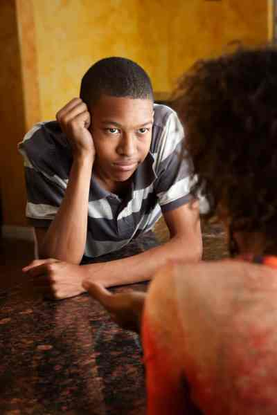 African American son looks smugly at mom during serious talk