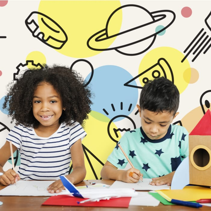 How Does the Brain Learn: A smiling black girl next to Hispanic boy, both doing schoolwork