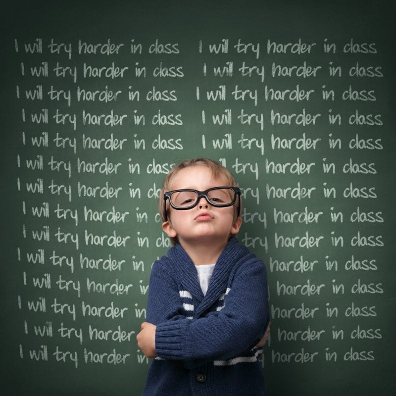Antagonistic teachers bully students. Defiant boy with glasses in front of blackboard: I will try harder in class