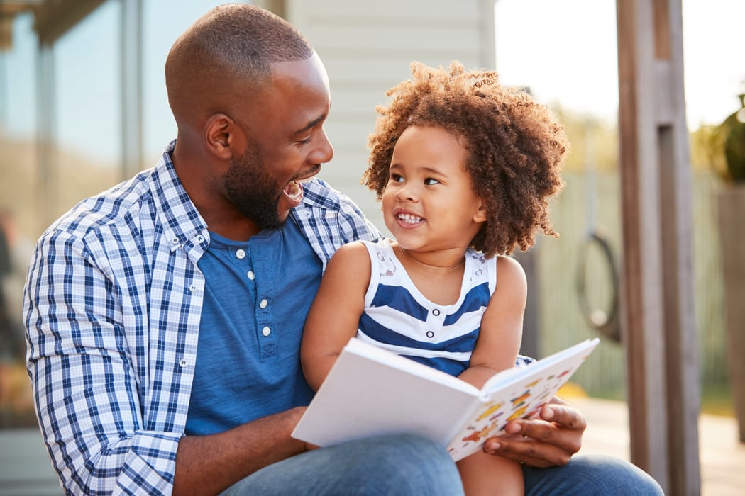 Black Father getting silly as he Reads to Daughter