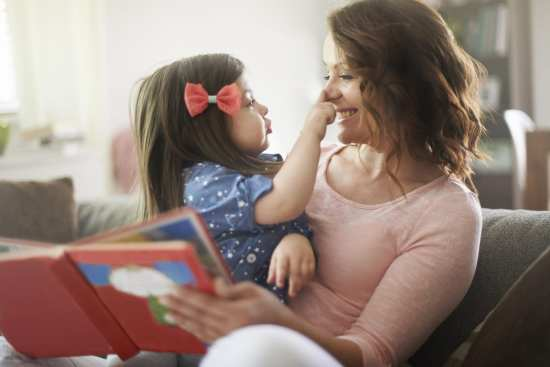 Little Girl touches smiling mothers nose as mom reads storybook