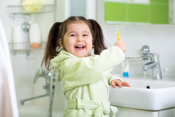 Smiling pigtailed girl holds up toothbrush