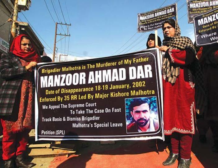 Bilkees (L) and her elder sister holding a banner demanding punishment for accused Major Kishore Malhotra.