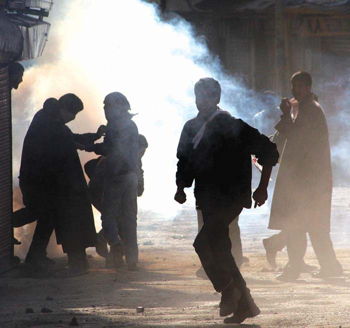 Youngsters run for cover after forces fired a tearsmoke shell in downtown Srinagar. Pic: Bilal Bahadur