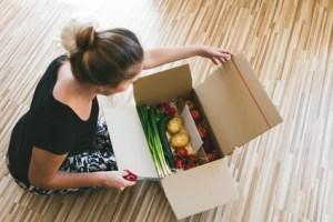 Frau ffnet Kiste mit Lebensmitteln, Lieferservice per postsend