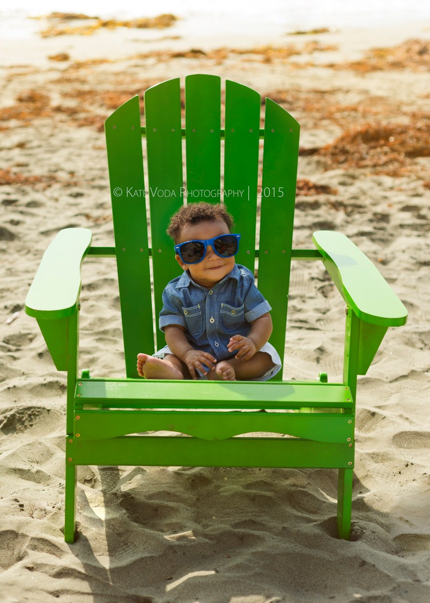 baby boy sitting in green adirondack chair