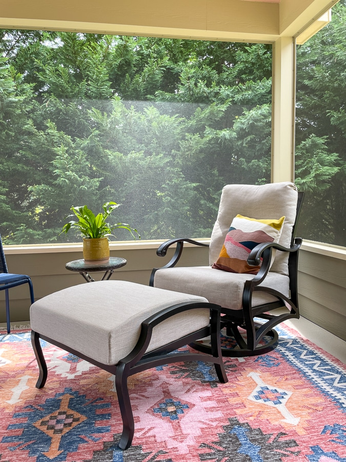 swivel rocker with west elm pillow and rug on screened in porch