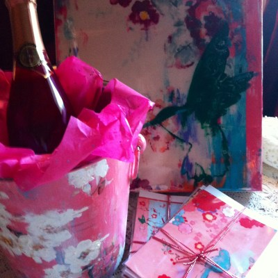 """Wine bucket with """"Pink Kiss"""" painting, pink champagne and two sets of Kathe Fraga greeting cards."""
