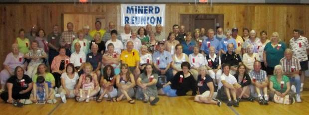 100th anniversary Minerd Reunion.  I am seated on the floor near the middle in a gray dress.  My stepmother Sharon is to the right in a black top and jeans.  My stepsister Lisa is to my left in a purple top.