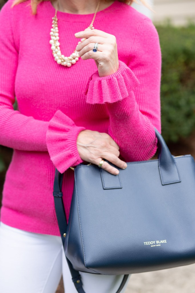 Wearing a bright pink flare cuff top with my new Teddy Blake navy handbag.