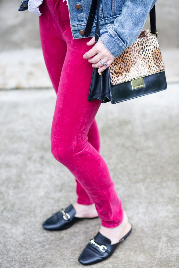 Pink skinny jeans with black loafer mules and a leopard bag.