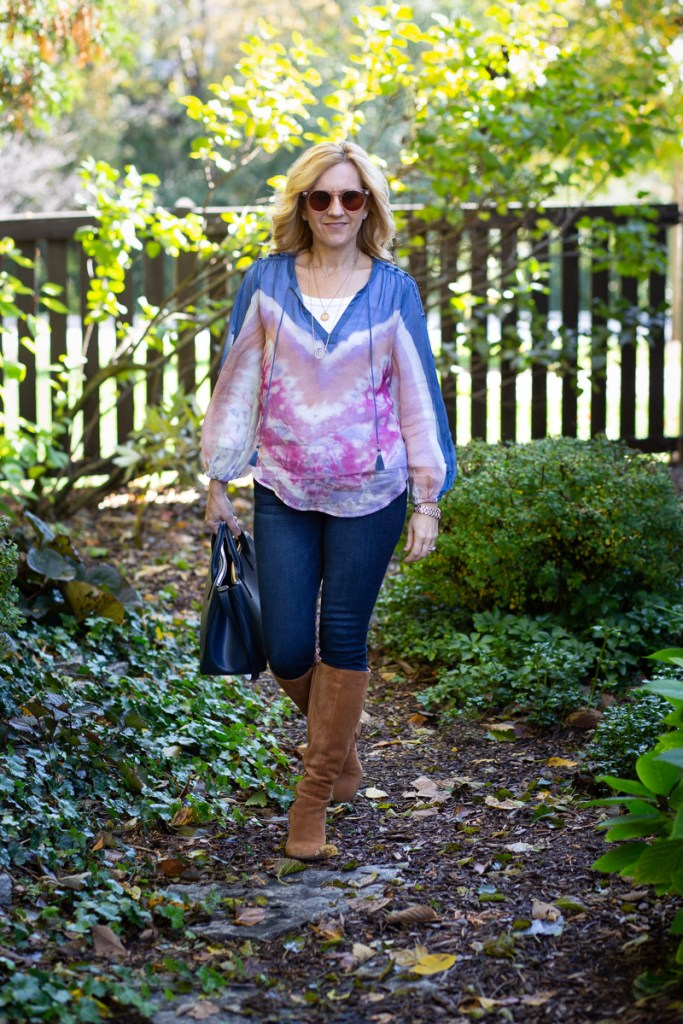 A beautiful tie-dyed watercolor blouse worn with dark skinny jeans and tan suede knee boots.