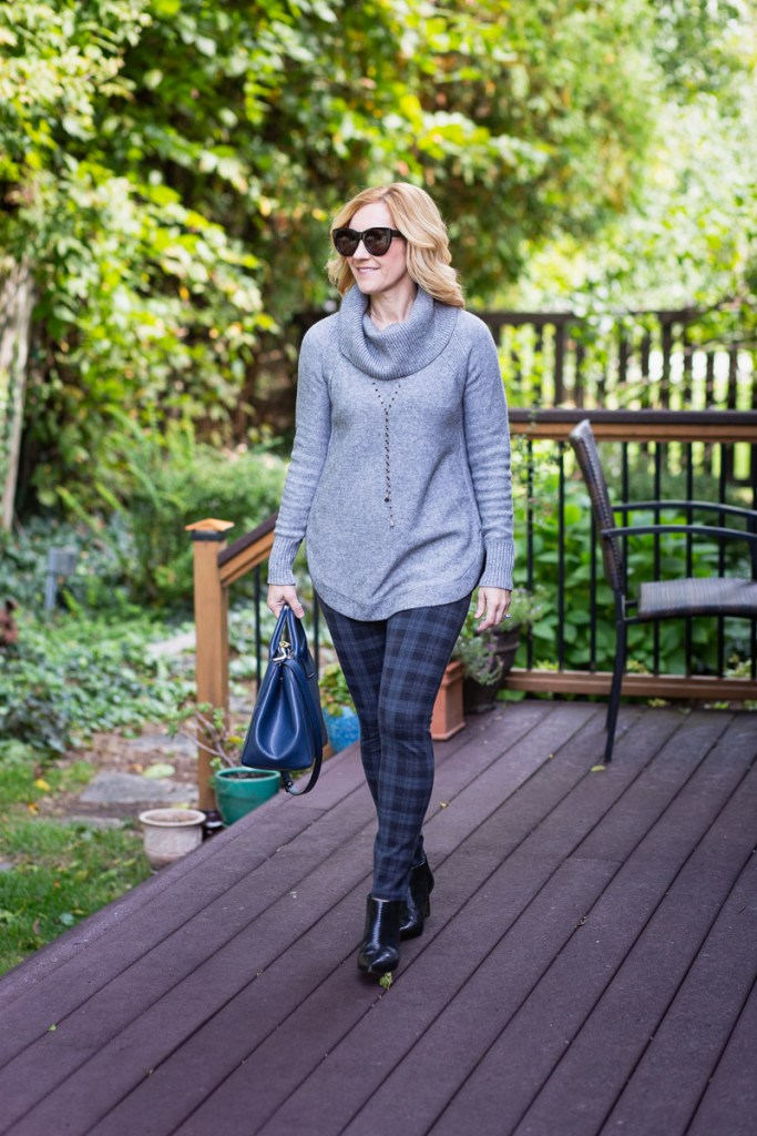 A grey cowl neck sweater paired with plaid leggings.