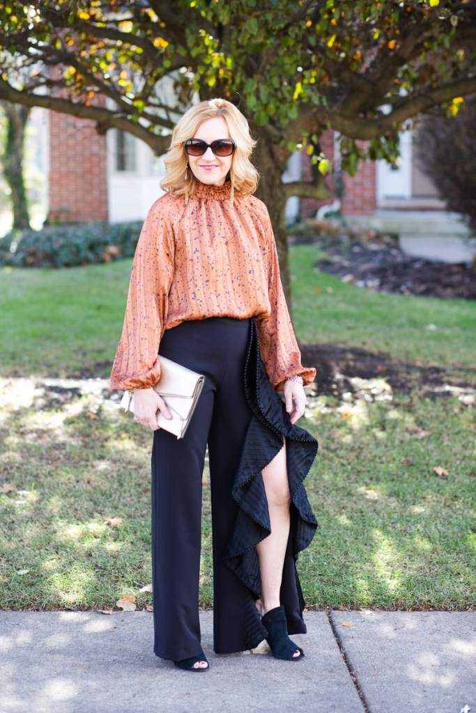 A Christmas outfit featuring ruffle pants and a long sleeve bodysuit.