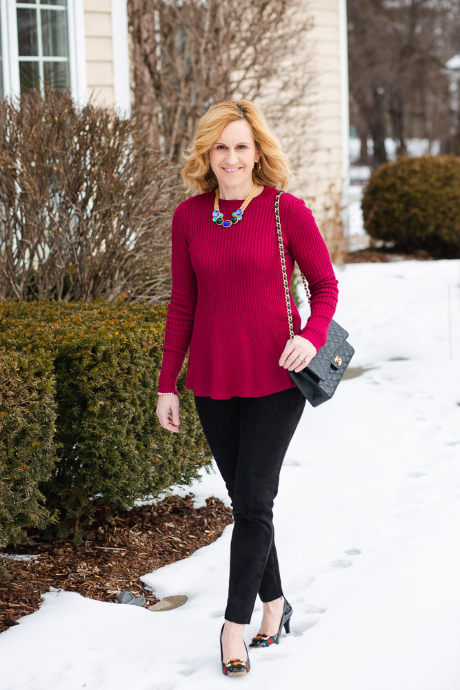 A red peplum sweater paired with faux suede leggings.