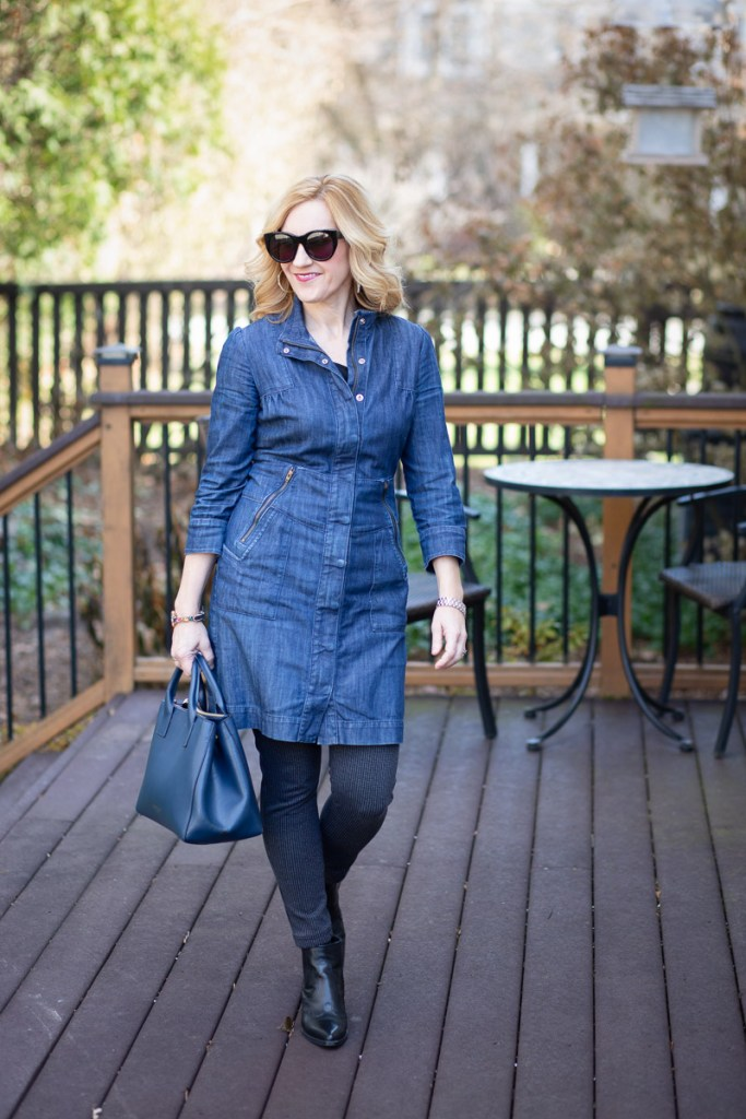 A winter look that layers printed leggings underneath a dress.