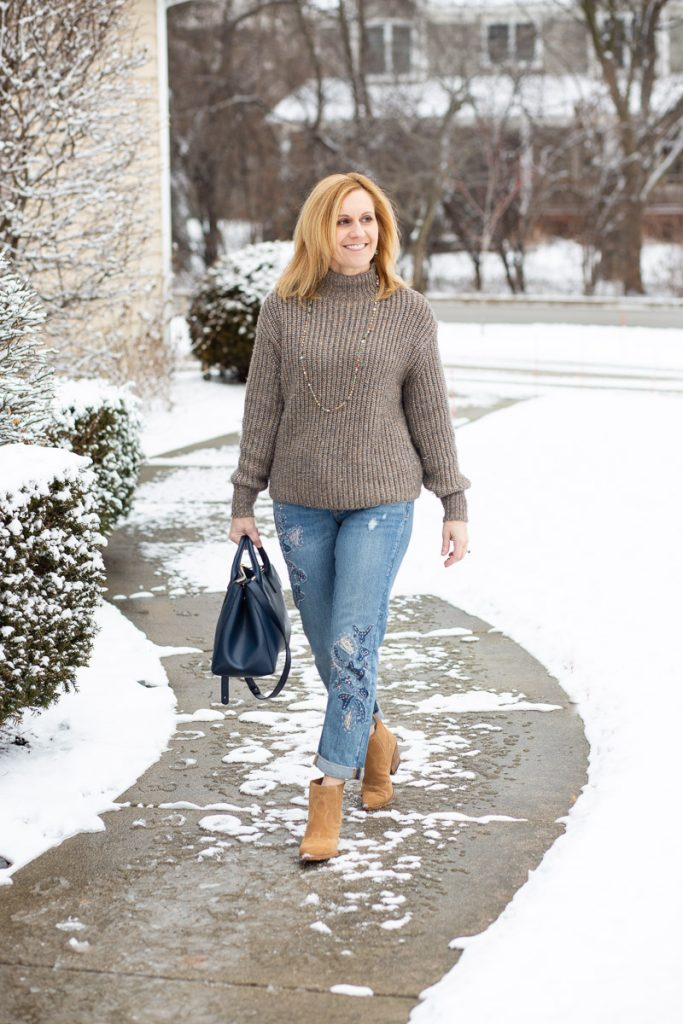 Pairing a neutral sweater with boyfriends jeans and suede booties.