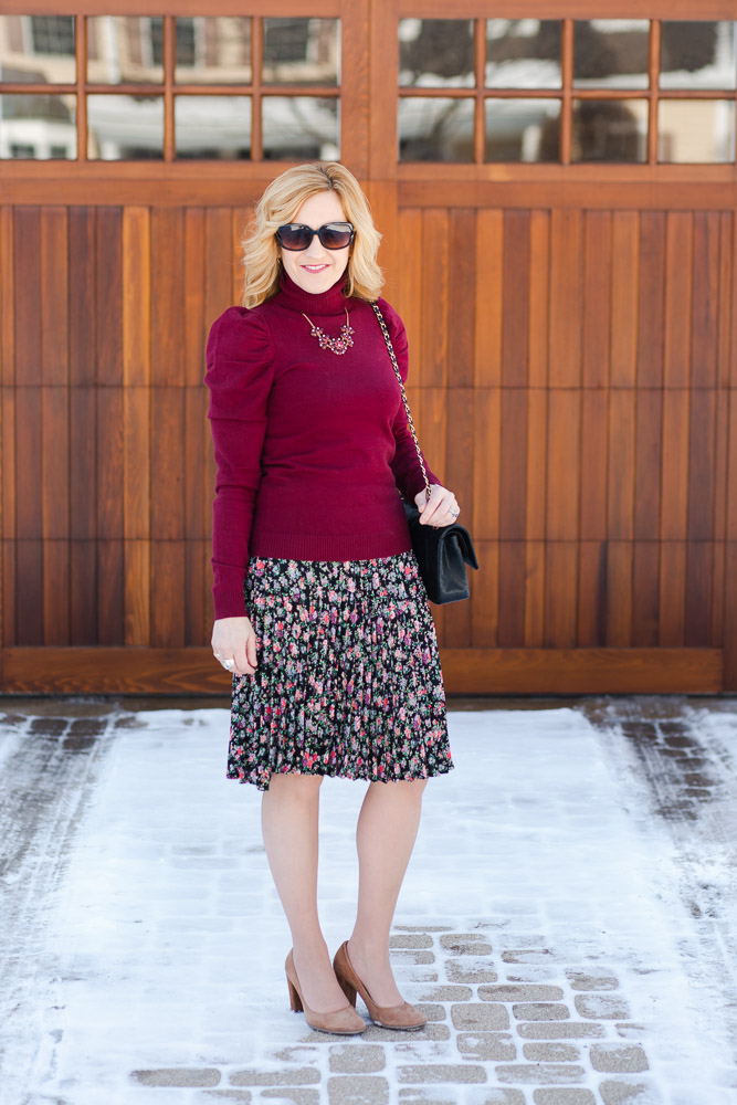 A puff sleeve turtleneck sweater paired with a dark floral pleated skirt.