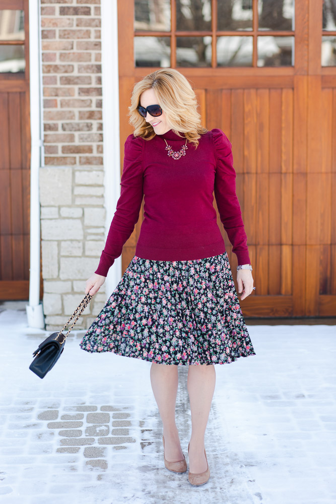 A chic winter look featuring a burgundy turtleneck and dark floral skirt.