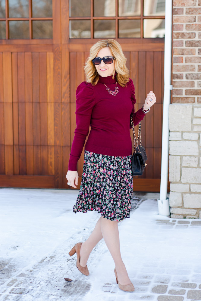 Styling a burgundy turtleneck with a pleated skirt and nude pumps.