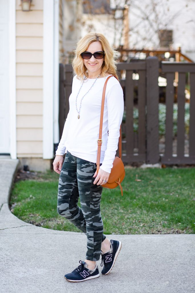 Camouflage corduroy jeans paired with a long sleeved white tee and sneakers.