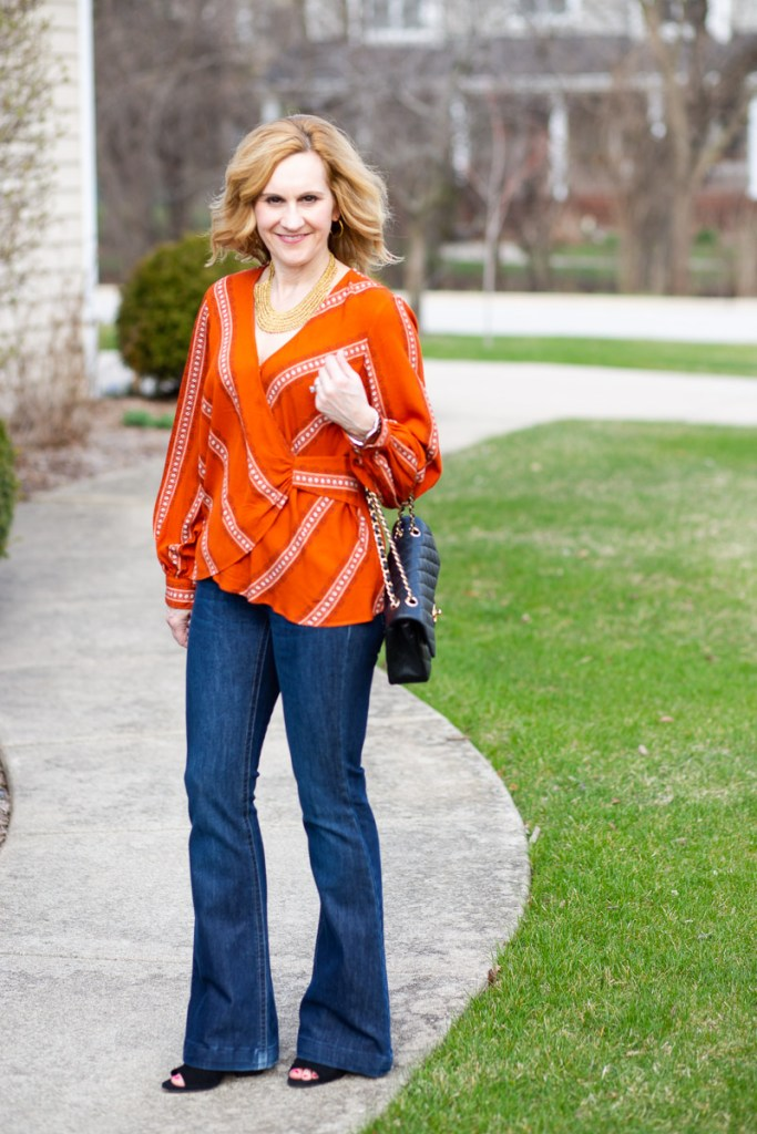 An elegant casual look featuring an dark orange long sleeved blouse and dark jeans